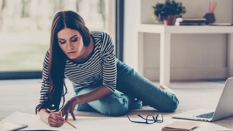 Woman multitasking between laptop and drawing