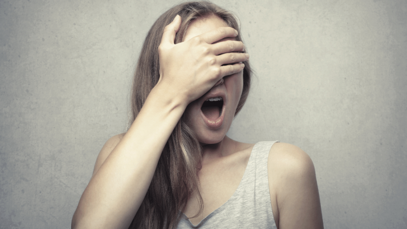 Woman covering face in fear of feedback