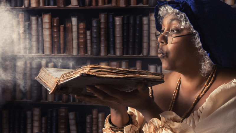Woman blowing dust off a book